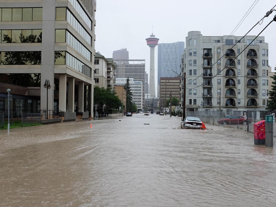 The Calgary tower hovers above a flooded west-side Calgary street on Friday June 21, 2013.