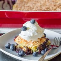 a slice of blueberry dump cake on a plate topped with a dollop of whipped cream and fresh blueberries