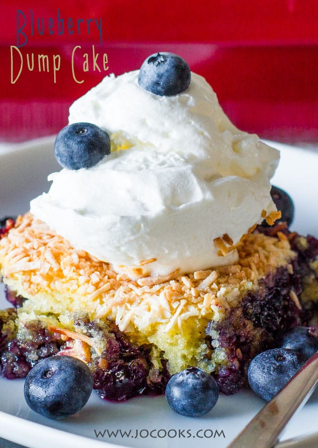 Close up shot of Blueberry Dump Cake with a dollop of whipped cream, surrounded by blueberries