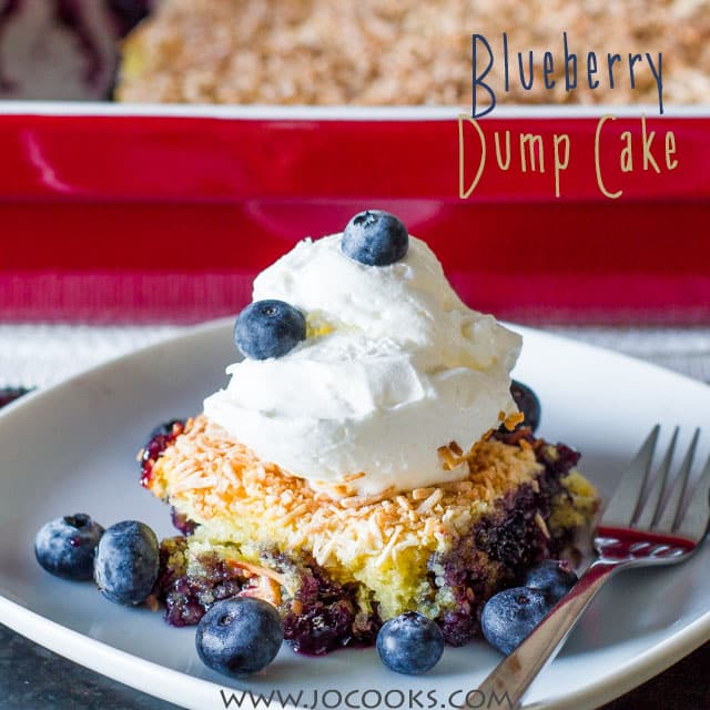 Slice of Blueberry Dump Cake with a dollop of whipped cream, surrounded by blueberries