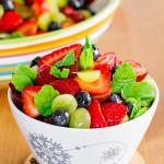 a bowl full of summer fruit salad with lemon dressing