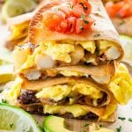breakfast quesadilla pieces stacked and garnished with chopped tomatoes.