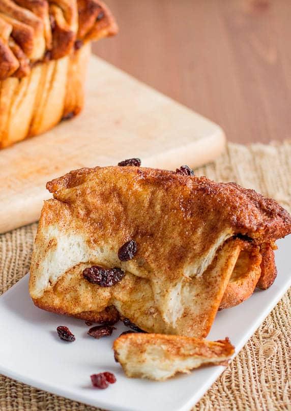 a piece of cinnamon brown sugar pull apart bread with raisins on a plate