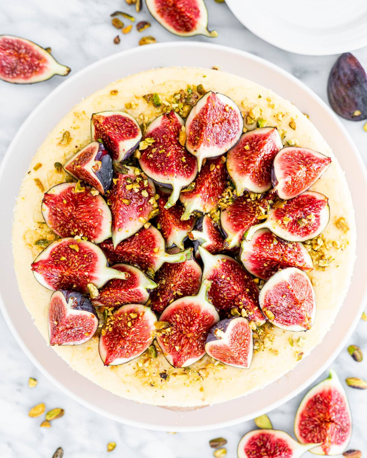 overhead shot of goat cheese cheesecake topped with figs, pistachios and honey