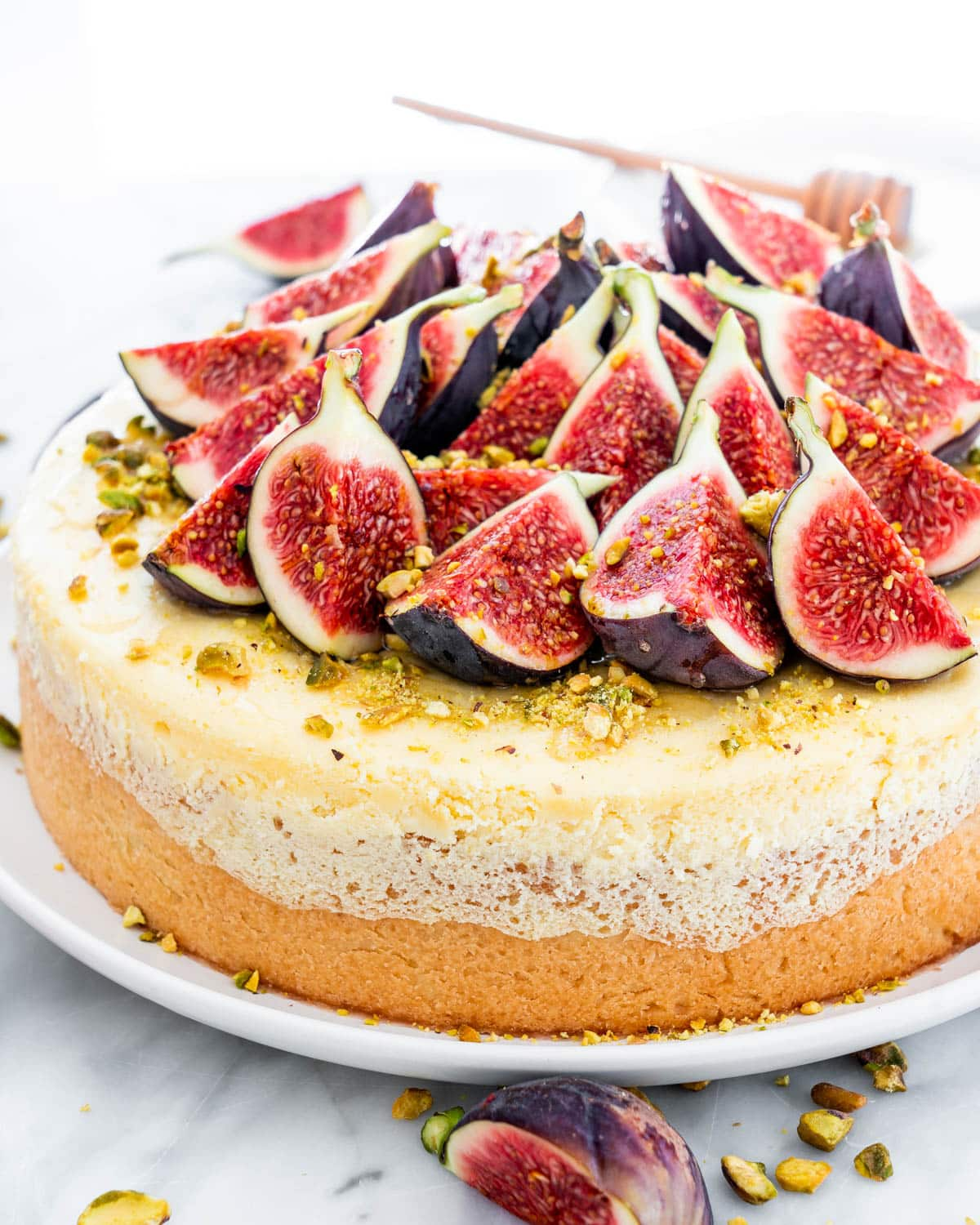 sideview of a goat cheese cheesecake topped with figs