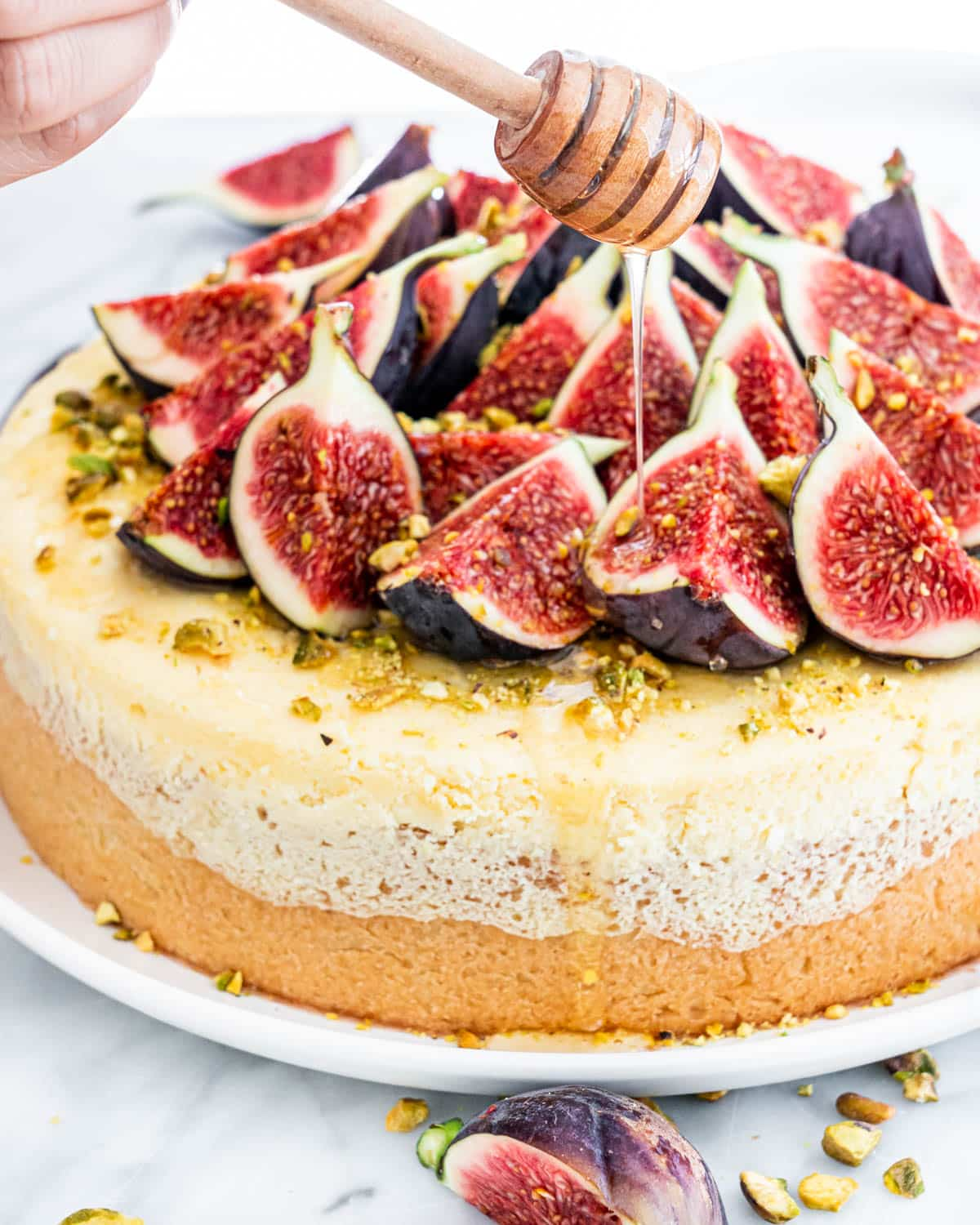 a hand drizzling honey over a cheesecake topped with cheese
