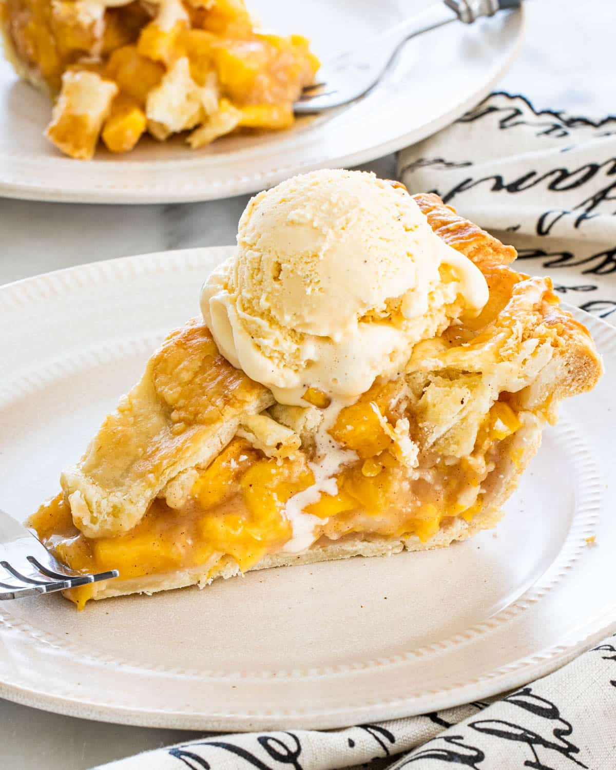 a slice of peach pie with a scoop of vanilla ice cream on it