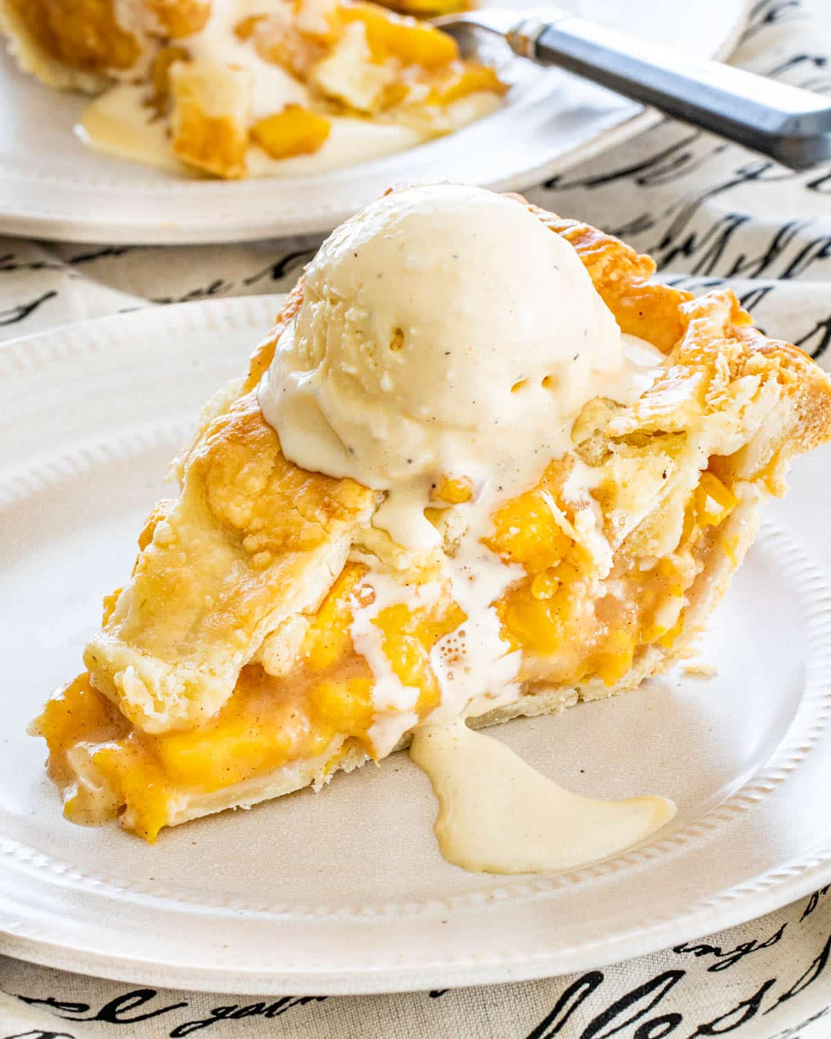 a slice of peach pie topped with vanilla ice cream