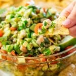 side view shot of a hand holding up a tortilla chip topped with shrimp avocado salsa