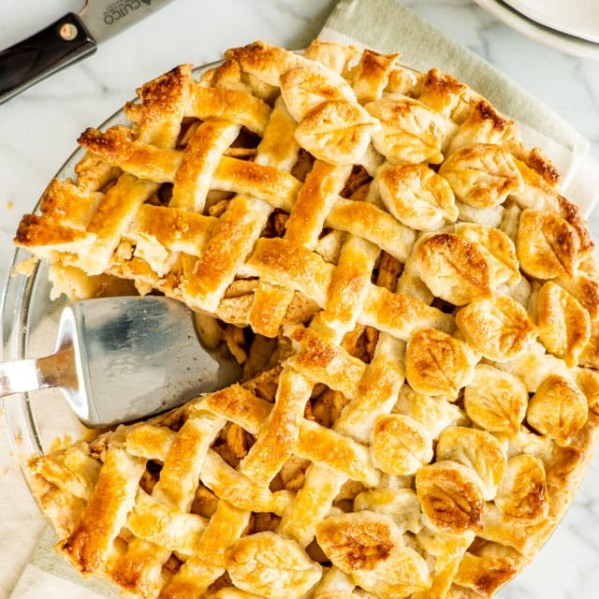 overhead shot of an apple pie with a slice missing and a pie lifter in the empty space