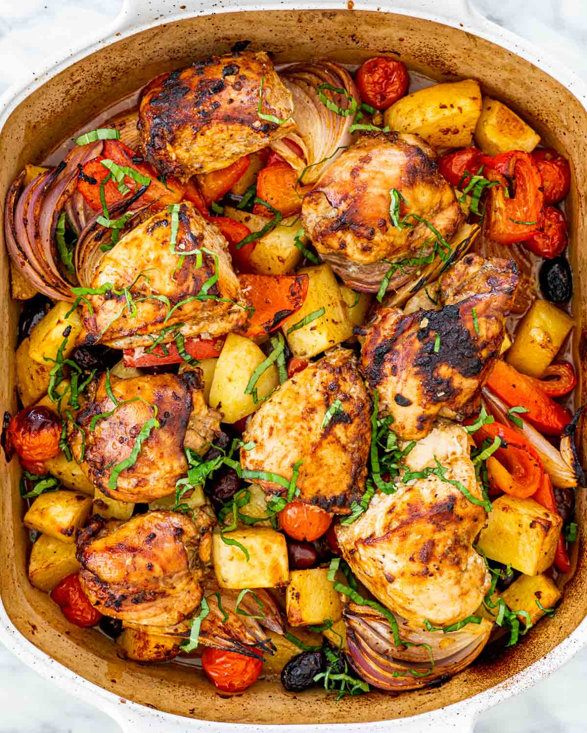 overhead shot of roasted chicken and vegetables in a baking pan