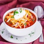 a bowl of beef chili topped with shredded cheese and a dollop of sour cream