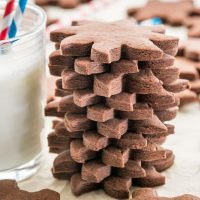 side view shot of a stack of chocolate sugar cookies stacked next to a glass of milk