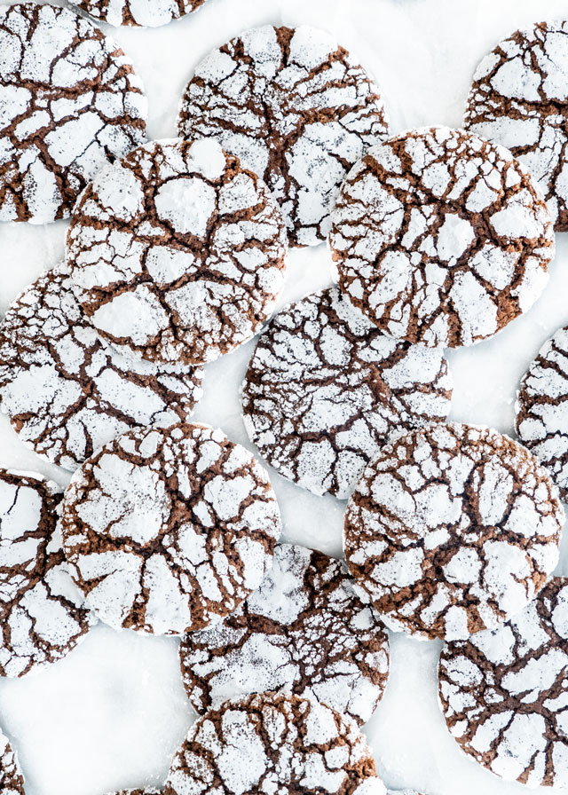 overhead shots of Chocolate Crinkle Cookies on parchmet paper