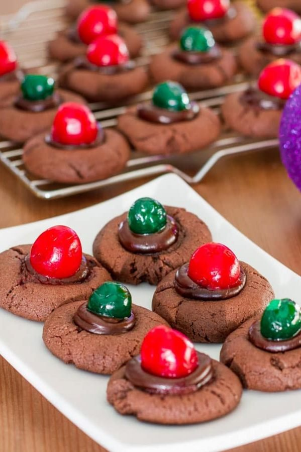 chocolate fudge cookies with cherries on top on a plate