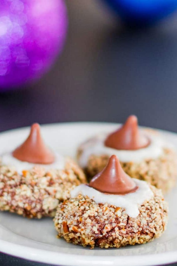 a plate of chocolate pecan thumbprint cookies topped with hershey kisses