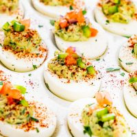 close up side view shot of guacamole deviled eggs lined up on a plate