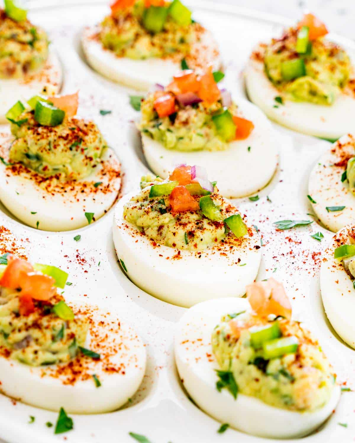 closeup of guacamole deviled eggs garnished with chili powder and cilantro