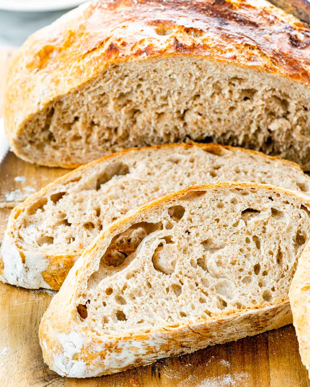 no knead whole wheat bread on a cutting board sliced.
