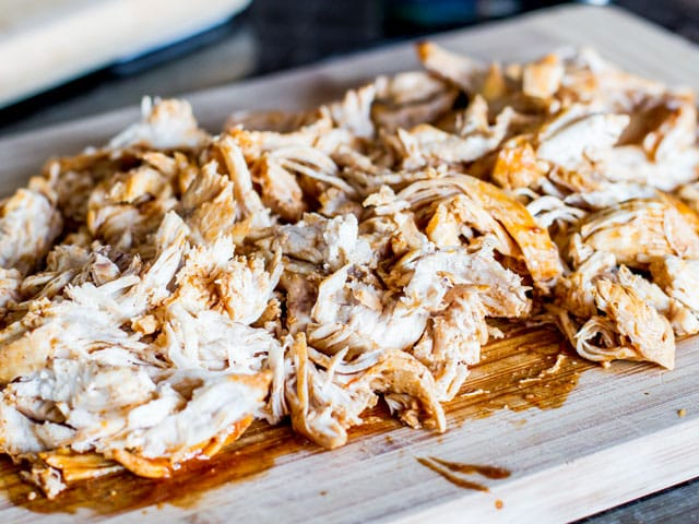 shredded chicken cooked in enchilada sauce on cutting board