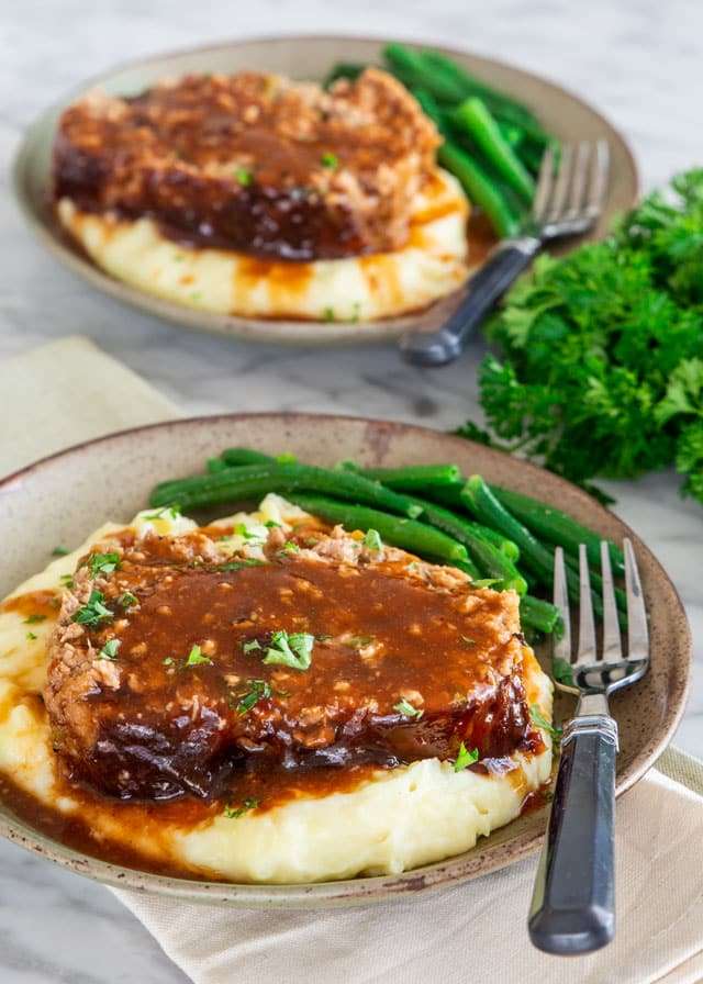 a slice of meatloaf over mashed potatoes