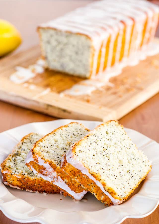 3 slices of lemon poppy seed bread on a plate with the loaf in the background
