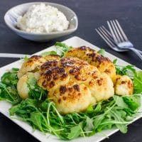 a roasted head of cauliflower on a bed of arugula