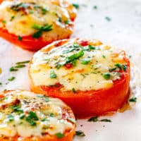 side view shot of 3 slices of baked parmesan tomatoes garnished with parsley