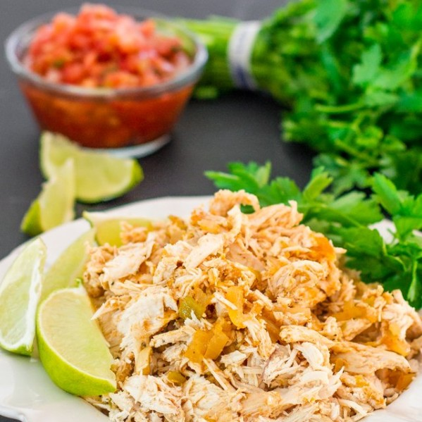 a plate of crockpot mexican chicken garnished with lime wedges