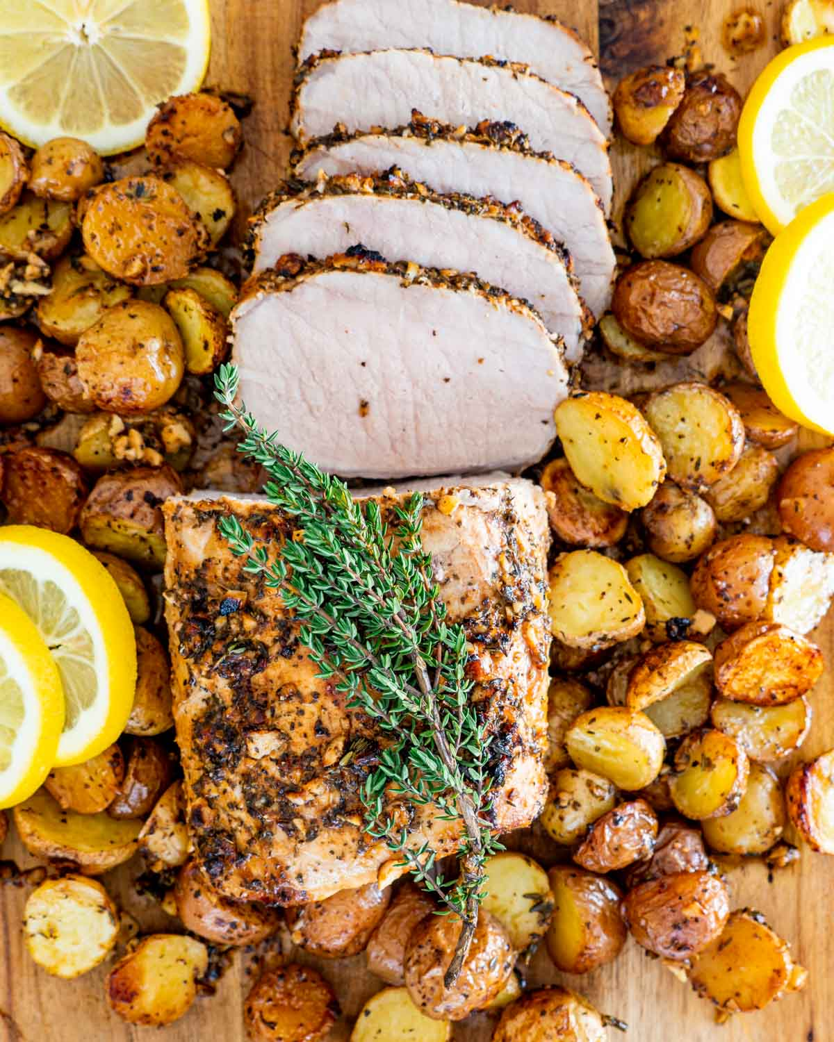 overhead shot of sliced lemon garlic pork roast with potatoes on a cutting board