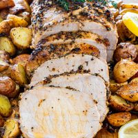 Sliced lemon garlic pork roast topped with a sprig of thyme, surrounded by roasted potatoes