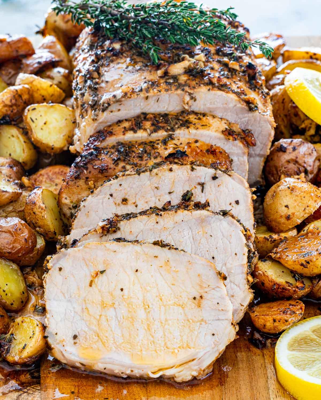 lemon garlic pork loin sliced on a cutting board with roasted potatoes