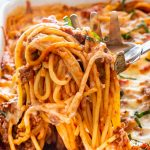 a spaghetti spoon taking a scoop of baked spaghetti casserole