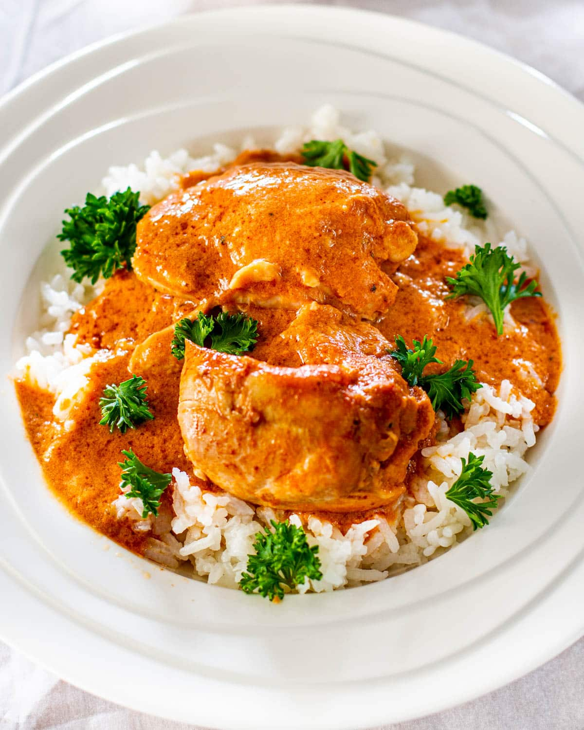 Crockpot Thai Chicken over a bed of rice garnished with parsley