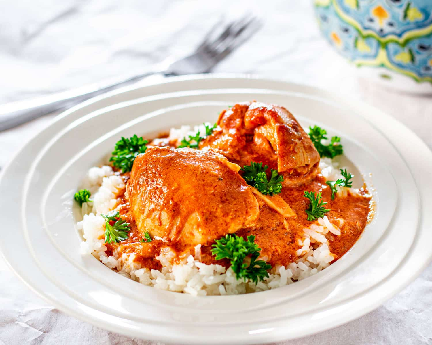 Crockpot Thai Chicken over a bed of rice in a white plate