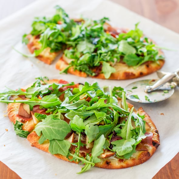 Finished Pear Prosciutto and Arugula Flatbreads with a pizza cutter on the side