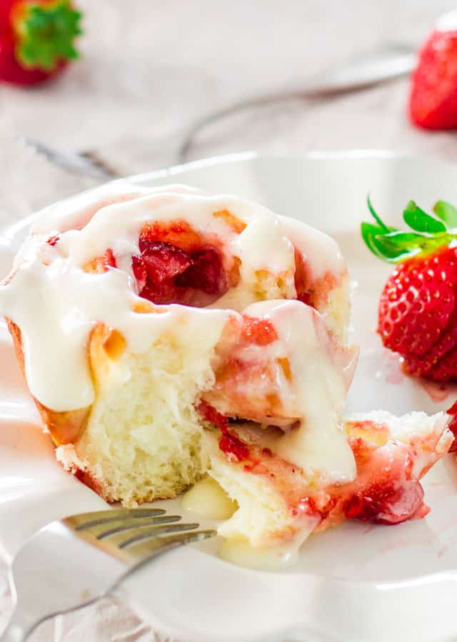 closeup shot of strawberry roll drizzled with cream cheese icing