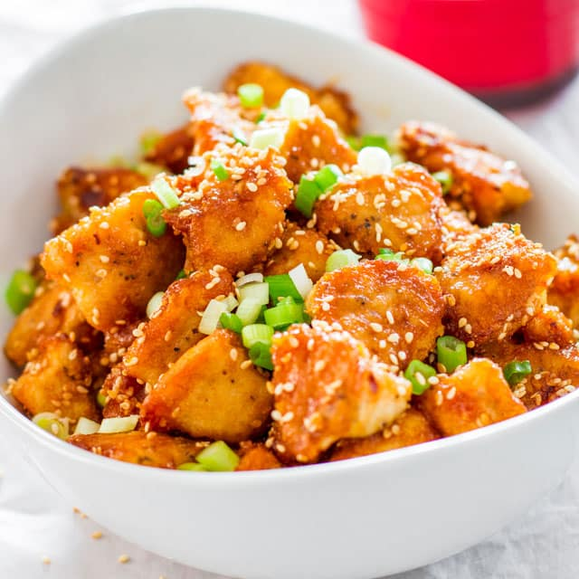 Sweet and sour chicken garnished with sesame seeds and green onions in a white bowl