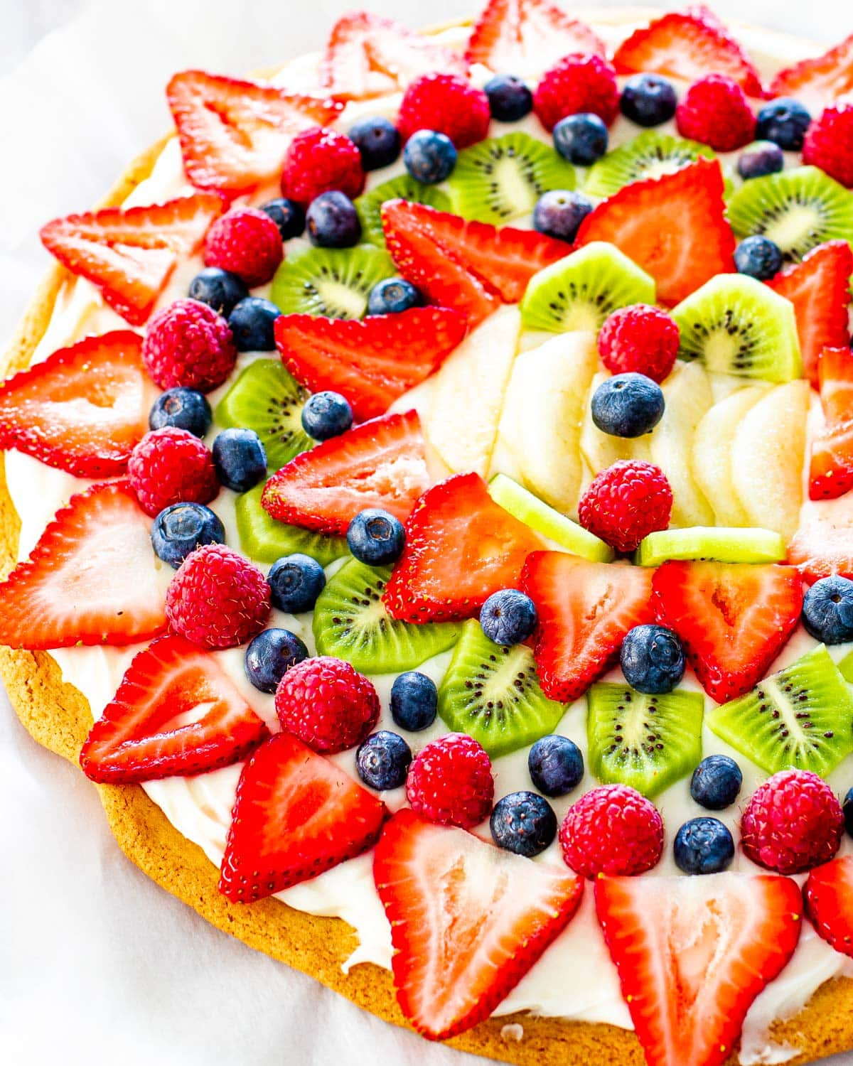 overhead shot of a beautiful fruit pizza on a cookie crust with cream cheese frosting