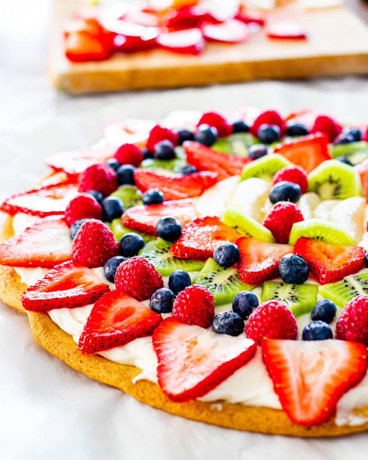 side shot of a beautiful fruit pizza on a cookie crust with cream cheese frosting