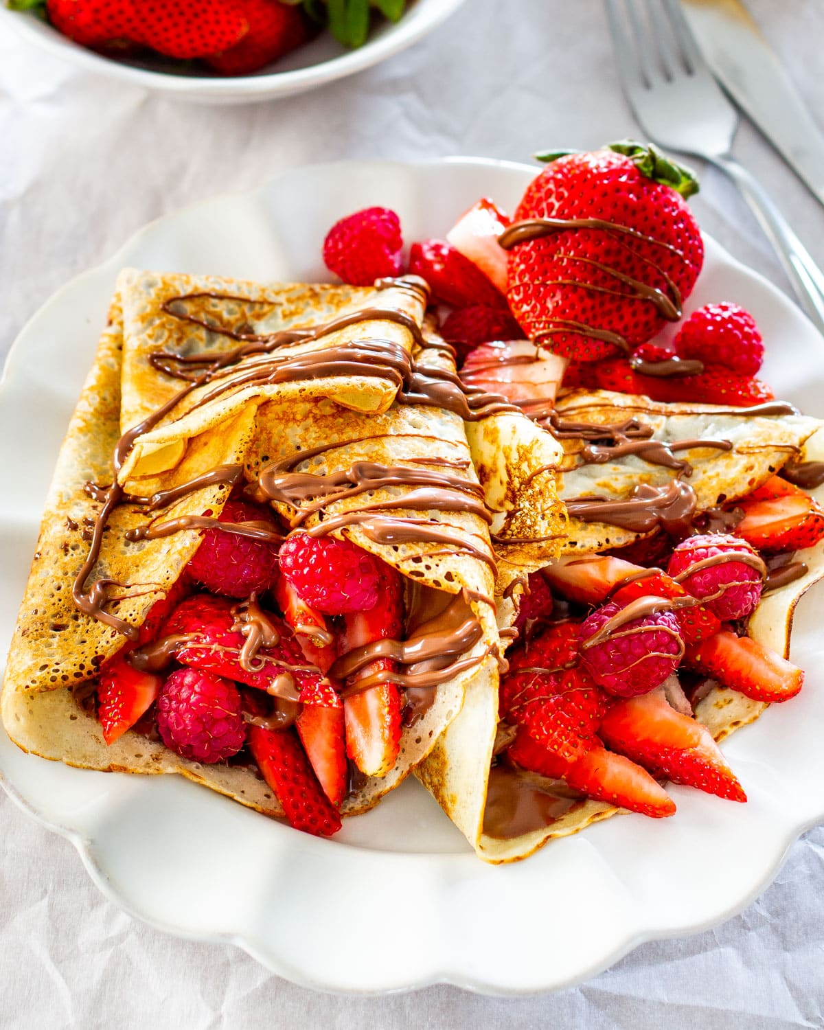 two homemade crepes stuffed with nutella and berries on a white plate