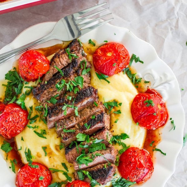 a plate with creamy polenta topped with grilled steak and roasted tomatoes
