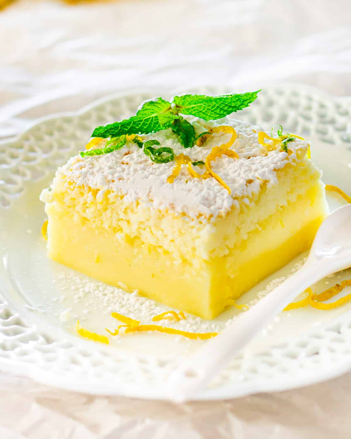 a slice of lemon magic cake on a white plate garnished with mint