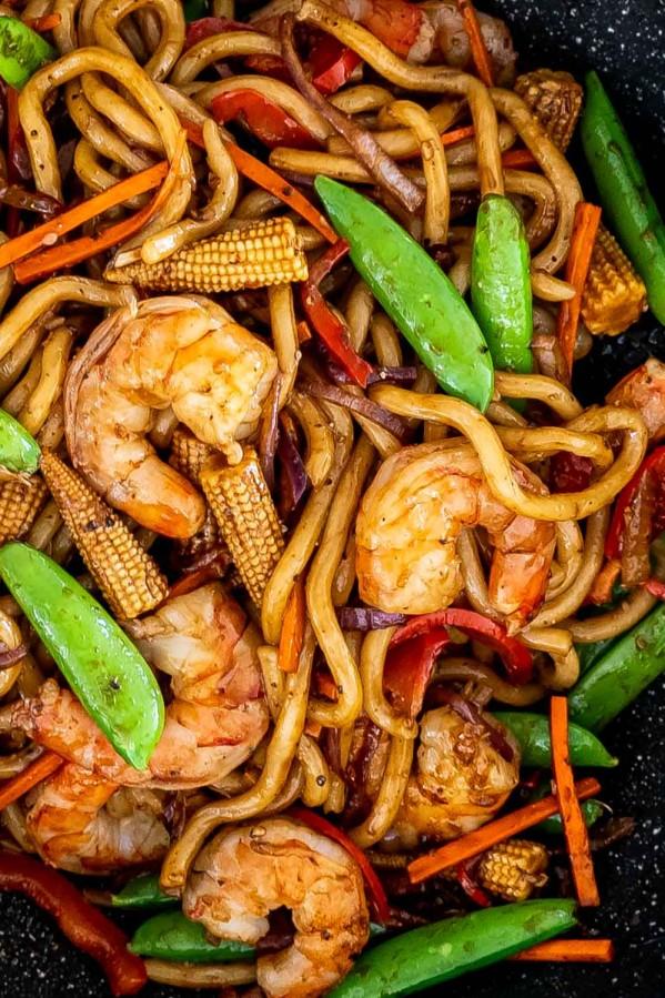 black pepper udon noodles with shrimp in a wok.