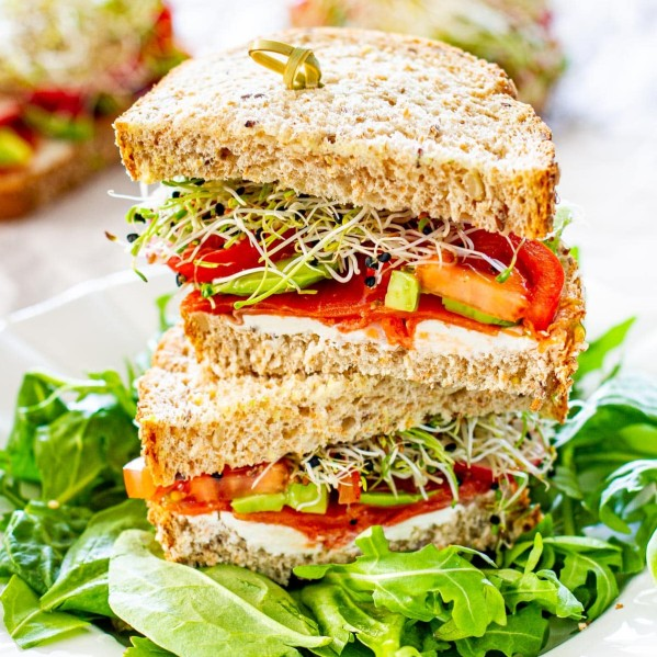 a smoked salmon loaded with veggies on whole grain bread cut in half and stacked on top of each other on a bed of arugula