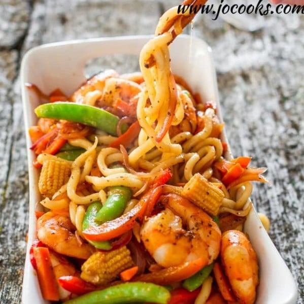 chopsticks picking up noodles from a bowl of spicy black pepper shrimp and udon noodles