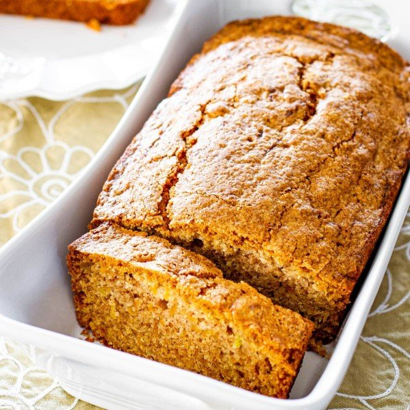 a cantaloupe tea loaf in a white loaf pan with a slice cut out