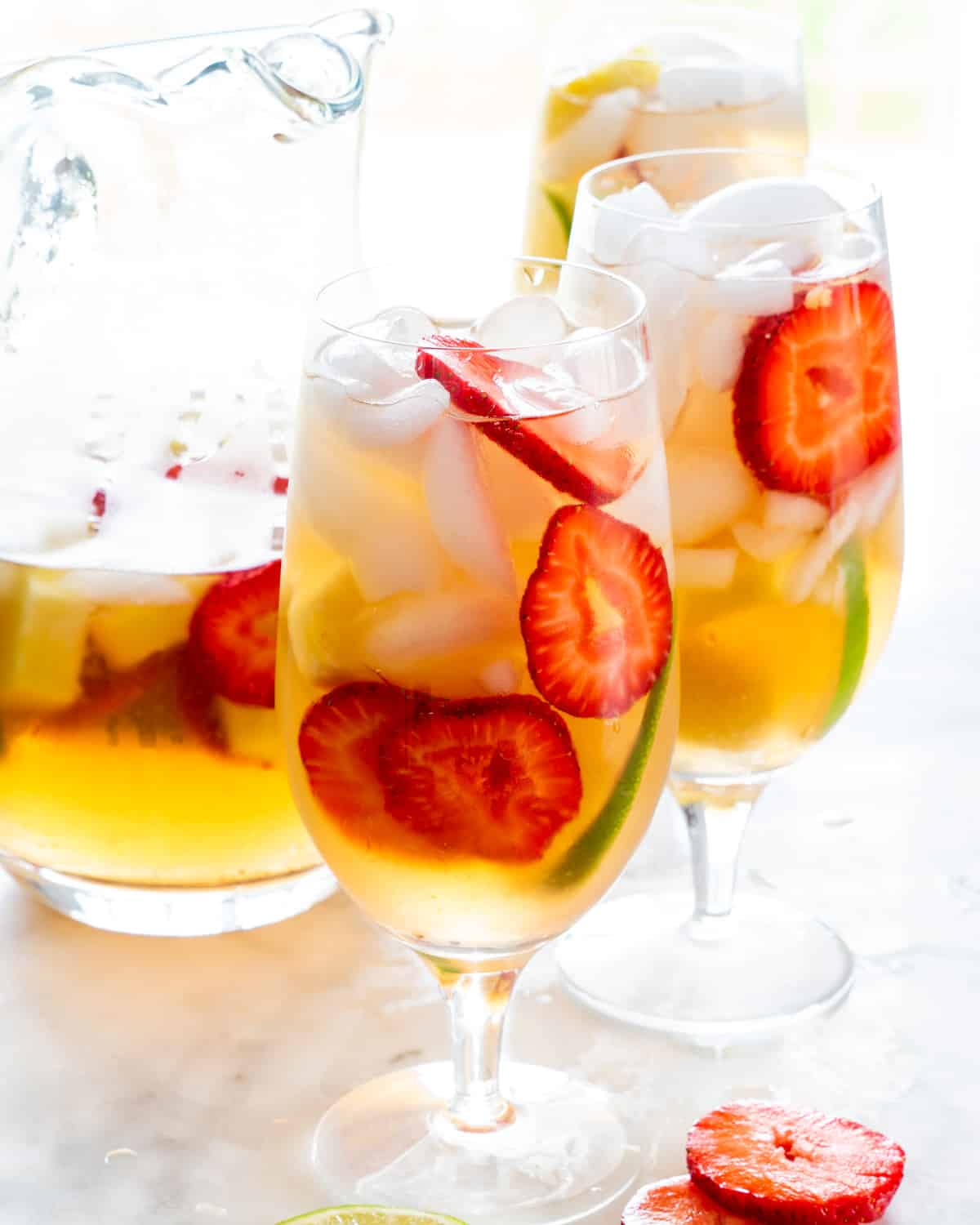 3 glasses of white sangria complete with fruits next to a pitcher of sangria