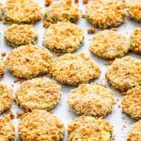 side view freshly baked parmesan zucchini crisps on a baking sheet