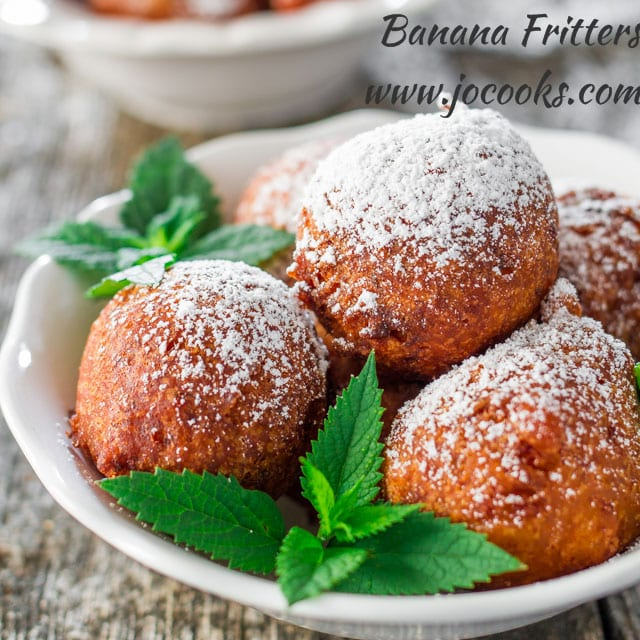 Banana fritters in a white bowl dusted with icing sugar with mint leaves as decoration